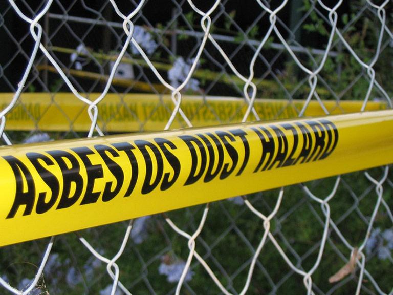 Fascia gialla intorno a recinzione con scritta Rischio Polveri Amianto